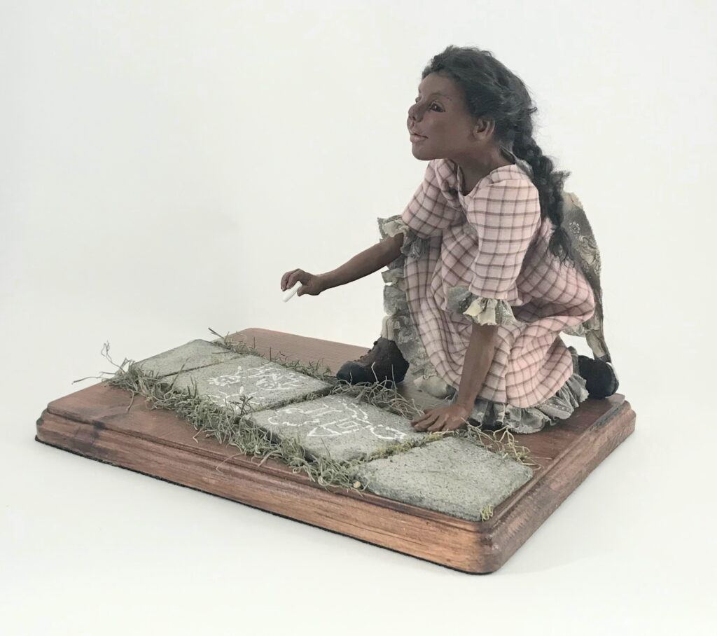 Young black girl doll writing on slate with chalk.